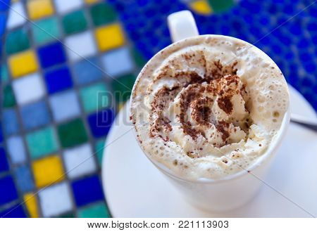 Cup of fresh hot cappuccino stands on a table in the style of Greek mosaic. Top view. stock photo