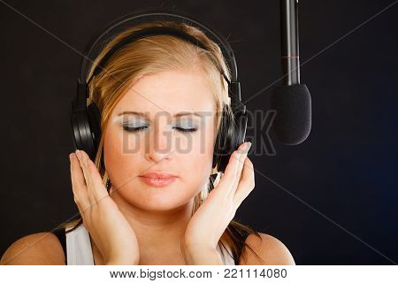 Music, passion, stage-fright concept. Blonde young woman singing to microphone and wearing big headphones on her head performing songs in studio.
