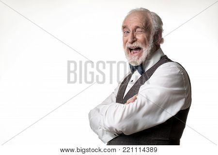 Portrait of jesting elderly man winking at camera with joy. Copy space in left side. Isolated on background