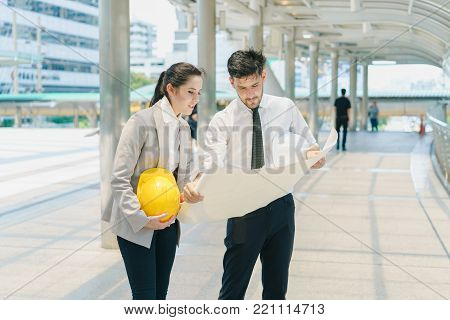 Businessman and Businesswoman look drawing blueprint together. Engineer meeting drawing discuss for work planning at construction site.