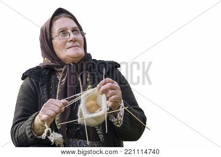 Masuleh, IRAN - December 22, 2017 close up portrait of an elderly woman knitting woolen sock isolated on white. Gilan Province