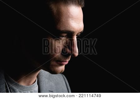 Feeling hopeless. Close-up profile of sad stylish young man is standing and looking down wistfully. Isolated background with copy space in the right side