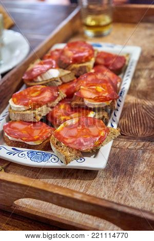 Chorizo And Goat Cheese Toasts on a Porcelain Plate on a Wooden Board