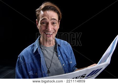 Full of joy. Portrait of optimistic young man is sitting and keeping fresh newspaper. He is looking at camera with wide smile. Isolated background