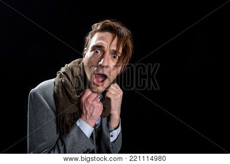 Portrait of astonished terrified young man is standing and looking at camera with eyes wide open. He is holding hands on collar while opening mouth and expressing dreadfulness. Isolated and copy space