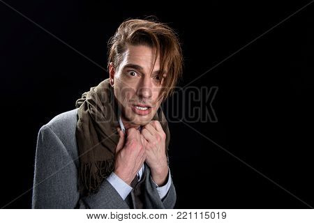 Portrait of scared stressful man is standing and looking at camera with terrify in wide-eyed. He is holding hands on his collar while expressing awfulness. Isolated and copy space in the right side