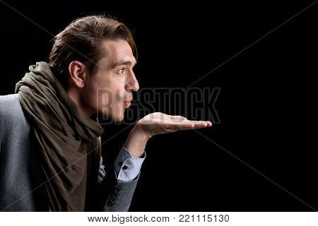 Air-kiss. Side view profile of elegant trendy young positive man is standing and holding palm up while sharing an air kiss. Isolated background and copy space in the right side