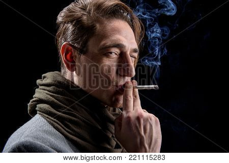 Need relax. Side view of young calm modish man is standing and smoking with pleasure. He is squinting on camera thoughtfully. Isolated on black background
