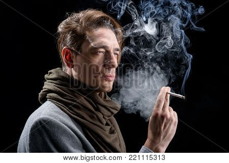 Miserable life. Side view of melancholic young stylish man is standing and smoking. He is looking aside wistfully while being in cloud of white smoke. Isolated background poster
