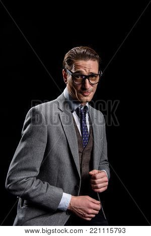 Being confused. Portrait of young man in official clothes is looking at camera embarrassedly while feeling unsure of himself. Isolated on dark background