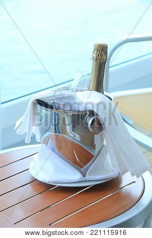 A bottle of champagne and glasses, waiting in a bucket to be served