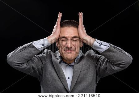 Overworked. Portrait of tired young businessman is feeling terrible headache. He is frowning face while standing with closed eyes and touching his head with pain. Isolated background