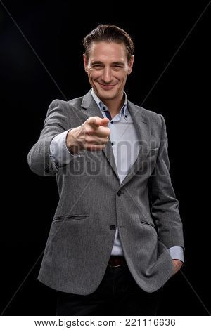 You. Portrait of positive young qualified businessman is standing and pointing finger while looking at camera with joy. He is holding right hand in pocket of his pants. Isolated background