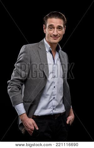 Wealthy and happy. Portrait of smiling young male entrepreneur is standing and looking at camera with joy. His hands in the pockets of his pants. Isolated on black background
