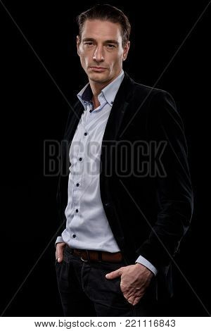 Unworthy of respect. Portrait of confident adult male entrepreneur wearing suit is standing with hands in pockets of his pants. He is looking at camera with disdain. Isolated on dark background