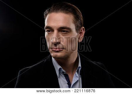 Feeling self-assured. Portrait of serene stylish young businessman is standing and looking aside confidently. Isolated background