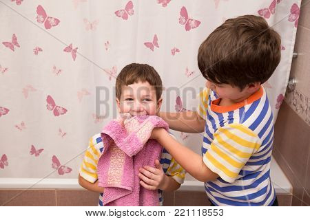 Older brother wipe his younger brother with pink towel in the bathroom