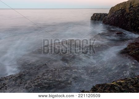 Waves Crashing Over Kelp on Maine Coast with long exposure effect