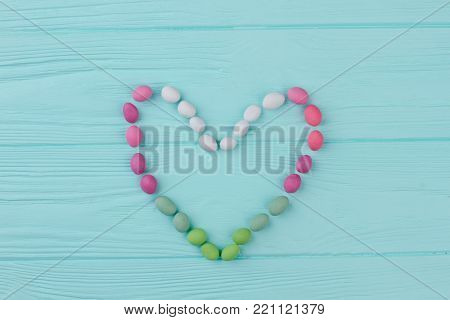 Love heart background, top view. Colorful candies on wooden background. Love and romance concept.