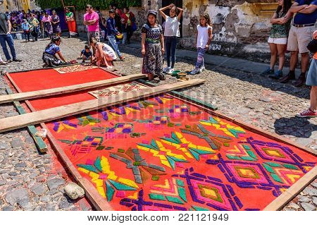 Antigua, Guatemala -  April 13, 2017: Making dyed sawdust carpet with Maya design for Holy Thursday procession in town with most famous Holy Week celebrations in Latin America