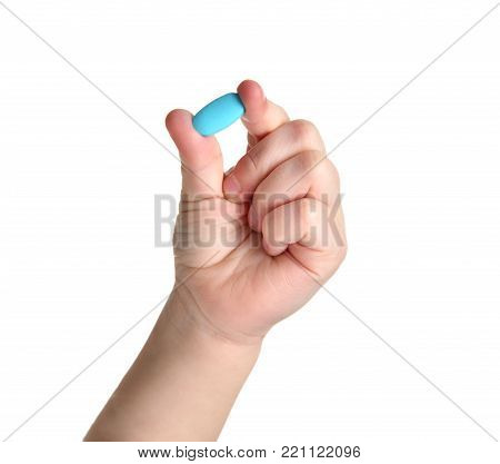 Young child baby kid hand hold blue pain killer tablet of medicine isolated on a white background