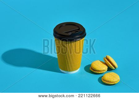 Hot coffee in yellow paper cup with black lid and macaroons on blue background with shadow, blurred and soft focus image. Still life. Copy space