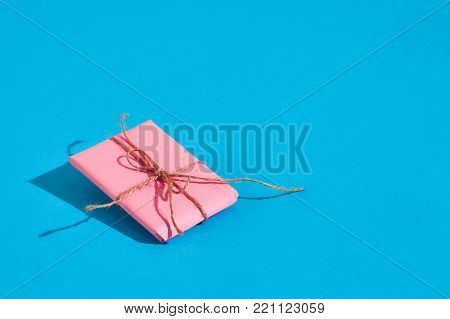 Pink gift box with thin tied rope with shadow on blue background. Still life. Copy space