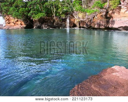 Waterfall flows into the ocean at Goat Island Marine Reserve on the North Island of New Zealand