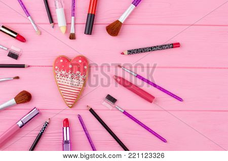 Decorative cosmetics beautiful composition. Make up brushes and accessories on wooden background. Heart shaped cookie on pink wooden table. Happy Valentines Day.