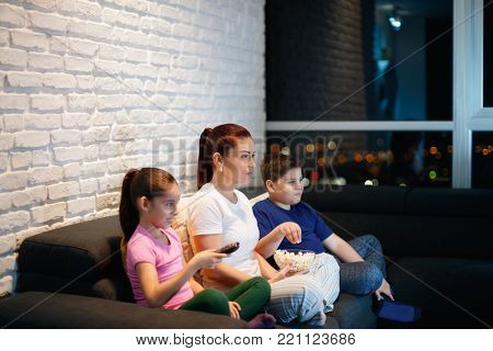 Movie night at home with divorced mother, daughter and son. Modern family watching television and eating popcorn, sitting on sofa at home. They laugh while watching comedy show on TV
