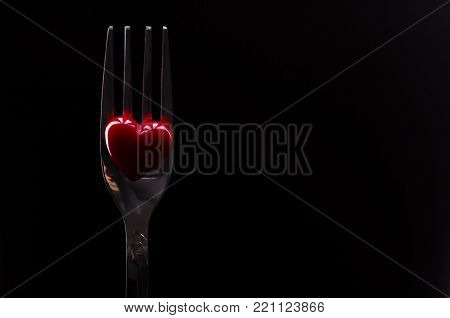 Steel shiny fork and red heart. Metallic fork and small red heart on black background, copy space. Romantic dinner concept.