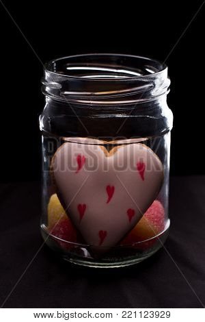Valentines Day cookie in glass jar. Glass jar with homemade heart shaped cookie on black background. Happy Valentines Day.
