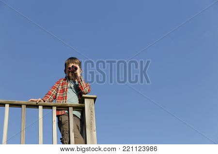 boy looking through binoculars against the blue sky. the child observes nature through binoculars. copy space for your text
