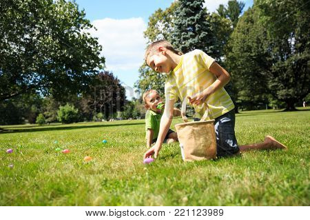children having fun collecting Easter eggs in the park. laughing  boys pick up colorful eggs. The concept of Easter Egg Hunt