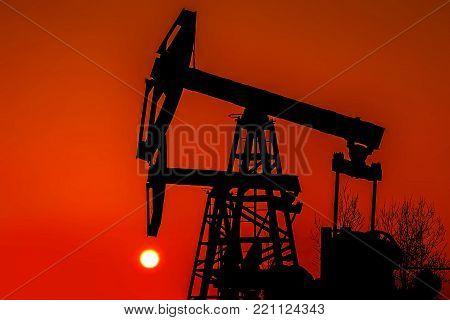 Oil pump at sunset. Industrial landscape. Inoperative Oil pump.