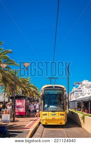 Adelaide, South Australia - February 28, 2016: Tram just arrived at Moseley Square in Glenelg with people from Entertainment Centre on a bright summer day. This is its termination point in the city of Holdfast Bay
