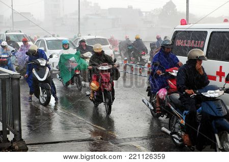 HO CHI MINH CITY, VIET NAM- NOV 21, 2017: Vietnamese  ride motorcycle, difficult move in heavy rain and high wind, couple soaking wet in bad weather by tropical low pressure after storm, Vietnam