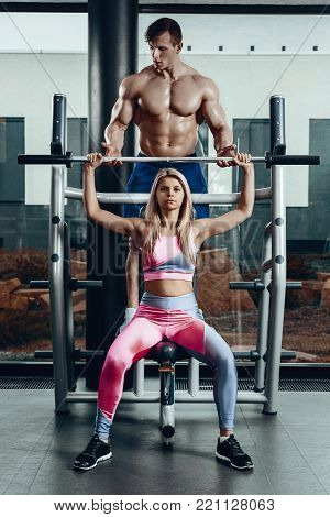 Sport, fitness, teamwork, bodybuilding and people concept - young woman and personal trainer with barbell flexing muscles in gym. Personal trainer with a gorgeous body without a T-shirt in the gym