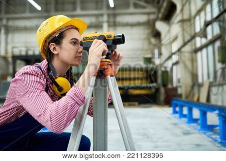 Side view portrait of young female geodesist wearing hardhat looking into optical level mounted on tripod at construction site, copy space