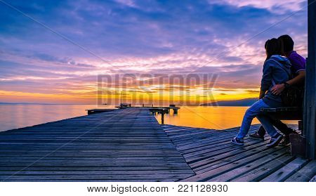 The romantic young couple is hugging on a wooden pier that stretched into the sea at sunrise and had a beautiful golden sky.