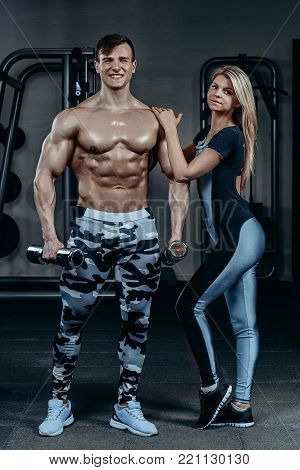 Fitness couple - woman and man with dumbbells in gym. Personal trainer with a gorgeous body without a T-shirt with young woman