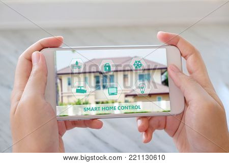 Hand using smart phone as smart home control application, smart home concept, technology and lifestyle