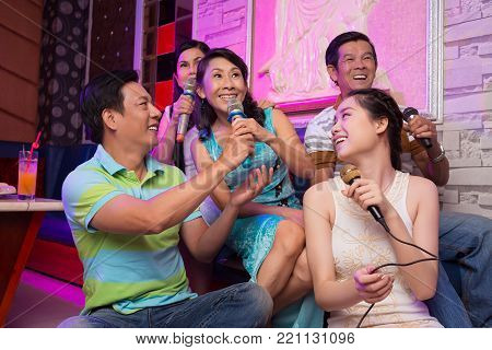 Asian man giving microphone his wife so she can sing