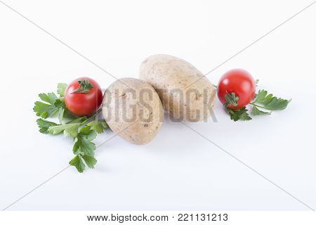 Potatoes and tomatoes on a white background. Potatoes on a white background. Red tomatoes with potatoes.