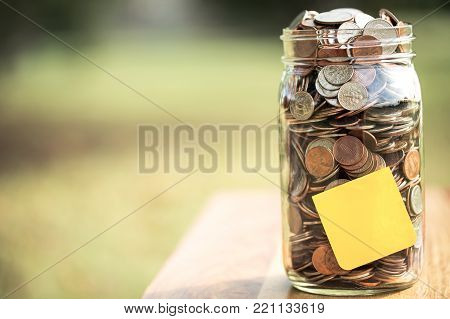 Mony jar outside with copy space and a sticky note.