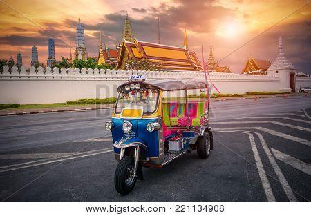 Tuk tuk on the background of Bangkok's Grand Palace Complex and Wat Phra Kaew, one of Bangkok's tourist attractions, Bangkok, Thailand
