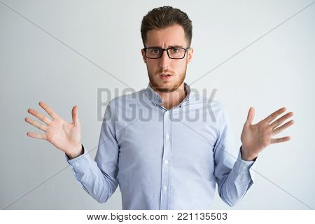 Portrait of upset or confused young Caucasian businessman wearing shirt and eyeglasses shrugging shoulders and looking at camera. Confusion and disappointment concept