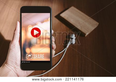 Hand holding mobile watching viral video advertising on phone screen at blur wood table,share video on social media concept,Digital marketing strategy