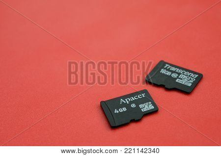 KHARKOV, UKRAINE - DECEMBER 29, 2017: Two small micro SD memory cards Apacer 4gb and Transcend 16gb lies on a red background. Illustrative editorial