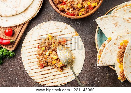 Homemade beef meat mexican fajitas with bell pepper, corn and tortilla over dark background, top view